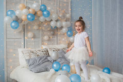 Little girl in a white air dress jumps on a bed royalty free stock images
