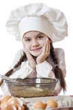 Little girl in a white apron breaks near the plate with eggs Royalty Free Stock Photography