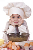 Little girl in a white apron breaks near the plate with eggs Royalty Free Stock Images