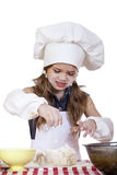 Little girl in a white apron and chefs hat knead the dough Stock Photo