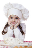 Little girl in a white apron and chefs hat knead the dough in th Stock Photo