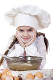 Little girl in a white apron and chefs hat knead the dough in th Stock Image