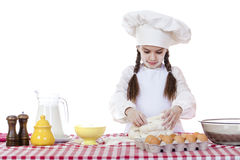 Little girl in a white apron and chefs hat knead the dough in th Royalty Free Stock Image