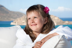 Little girl in white bathrobe relaxing on terrace Royalty Free Stock Photography