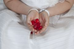 Communion girl dressed in white with hearts in her hands. Little girl of white beast communion with hearts in her hands Stock Photo