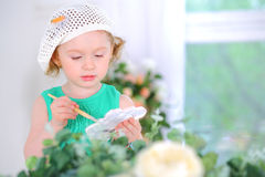 Little girl in white beret with watercolor paints Royalty Free Stock Images