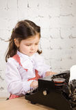 Little girl  prints on the ancient typewriter Royalty Free Stock Image
