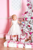 The girl at the Christmas fir-tree with gifts Stock Photo