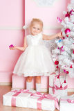 The girl at the Christmas fir-tree with gifts Royalty Free Stock Photography