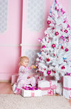 The girl at the Christmas fir-tree with gifts Royalty Free Stock Photos