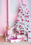 The girl at the Christmas fir-tree with gifts Royalty Free Stock Image