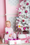 The girl at the Christmas fir-tree with gifts Stock Photos