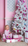 The girl at the Christmas fir-tree with gifts Stock Image