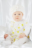 Little girl in white clothes, who sits on white coverlet Stock Photo