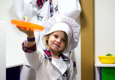 Little girl in white cooking clothes playing with plate Royalty Free Stock Photos