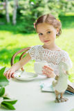 Little girl with white cup outdoor. Stock Photography