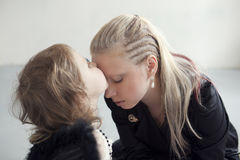 Little girl in white dress with artificial black wings kisses her mother in the forehead Royalty Free Stock Images