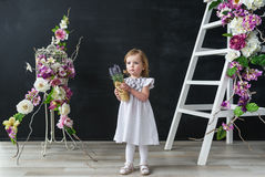 Little girl in a white dress. Baby girl with beautiful flowers stand in flowers room. Stock Image