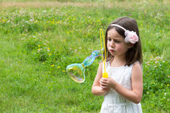 Little girl in white dress blowing bubbles at the park.  Royalty Free Stock Image