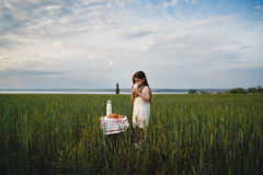 Little girl in white dress drinking milk in green field. Summertime. Evening. royalty free stock photo