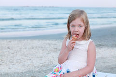 A little girl in white dress eating ice cream. Stock Images