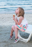A little girl in white dress eating ice cream. Royalty Free Stock Photography