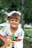Little girl in a white dress with embroidery. Little girl with blond hair and white dress sitting in the park and smiling Royalty Free Stock Photography