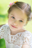 Little girl in white dress and flower. Stock Photos