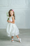 Little girl in white dress and flower is posing Royalty Free Stock Photos