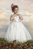 Little girl with white dress on grass Royalty Free Stock Photo