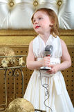 A little girl in white dress with microphone Royalty Free Stock Photos