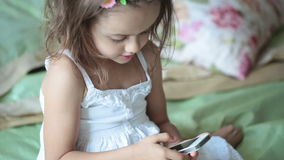 Little girl in white dress with mobile phone Stock Photo