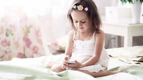 Little girl in white dress with mobile phone Royalty Free Stock Photos