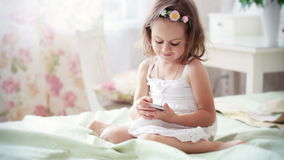 Little girl in white dress with mobile phone Royalty Free Stock Photography