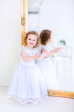 Little girl in a white dress next to a mirror Stock Photo