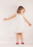 Little girl in white dress and pink shoes Stock Photos