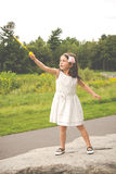 Little girl in white dress playing with bubble maker in the park Royalty Free Stock Photos