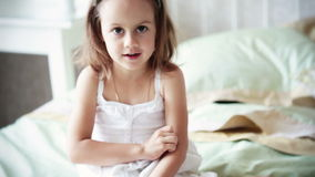 Little girl in white dress is speaking to somebody Royalty Free Stock Photography