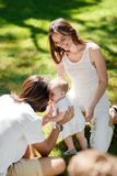 Little girl in the white dress try to make her first steps on the lawn while her parents smile and help her. stock images