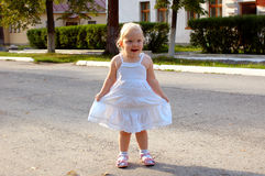 Little girl in white dress walk on the road. Stock Images