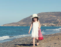 Little girl in white dress walking alone the sea Stock Photo