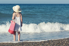 Little girl in white dress walking alone the sea, playing on the seashore Royalty Free Stock Photo