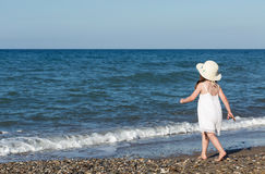 Little girl in white dress walking alone the sea, playing on the seashore Royalty Free Stock Images