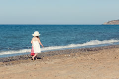 Little girl in white dress walking alone the sea, playing on the seashore Stock Image