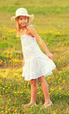 Little girl in white dress walking on the meadow Royalty Free Stock Photography