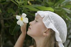 LITTLE GIRL AND WHITE FLOWER. Little girl smelling tropical flower in a garden Royalty Free Stock Image