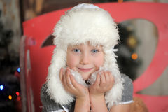 Little girl in a white fur hat and snow in the hands Stock Photos