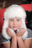 Little girl in a white fur hat and snow in the hands Royalty Free Stock Photos