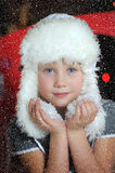 Little girl in a white fur hat and snow in the hands Royalty Free Stock Photography