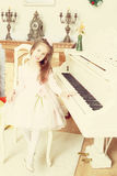 Little girl at a white Grand piano. Stock Photo